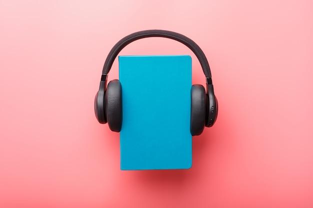 Hoofdtelefoon wordt gedragen op een boek in een blauwe hardcover op een roze achtergrond, bovenaanzicht.