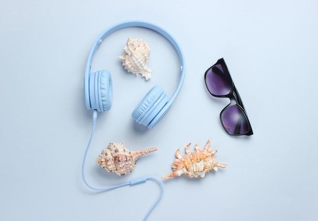 Hoofdtelefoon, zonnebril, schelpen op grijze achtergrond