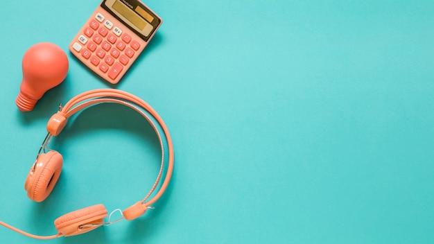 Hoofdtelefoons, calculator en gloeilamp op blauwe achtergrond
