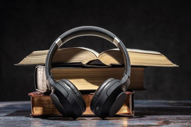 Hoofdtelefoons die naast oude boeken liggen. audioboek-concept.