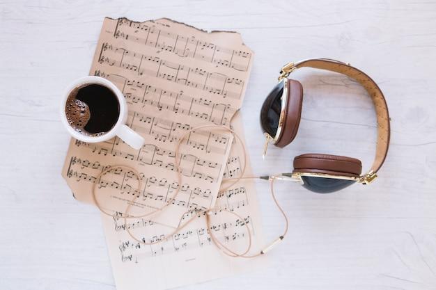 Hoofdtelefoons en koffie in de buurt van bladmuziek