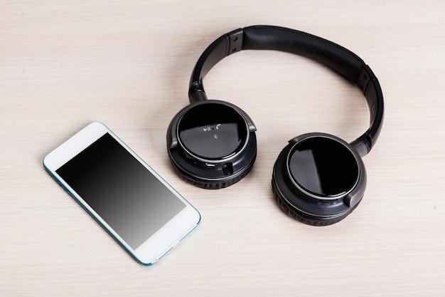 Hoofdtelefoons en smartphone op houten