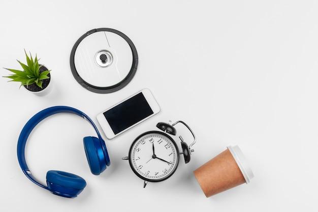 Hoofdtelefoons en wekker op witte achtergrond wordt geïsoleerd die. bovenaanzicht