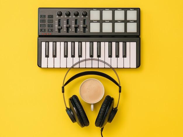 Hoofdtelefoons, koffiekop en muziekmixer op gele achtergrond. het concept van werkplekorganisatie. apparatuur voor het opnemen, communiceren en luisteren naar muziek.