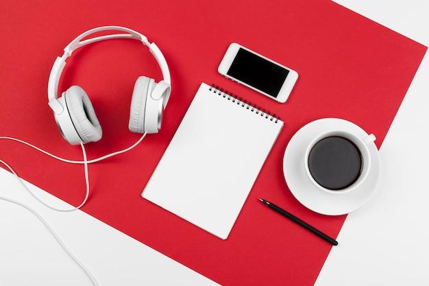 Hoofdtelefoons met koord op rode en witte kleurenachtergrond
