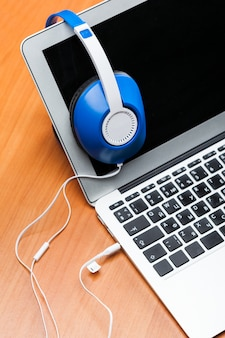 Hoofdtelefoons met laptop op tafel close-up