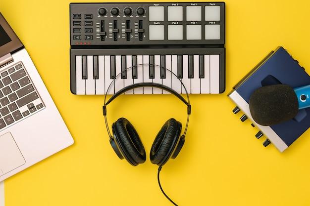 Hoofdtelefoons op muziekmixer, laptop en geluidskaart op geel