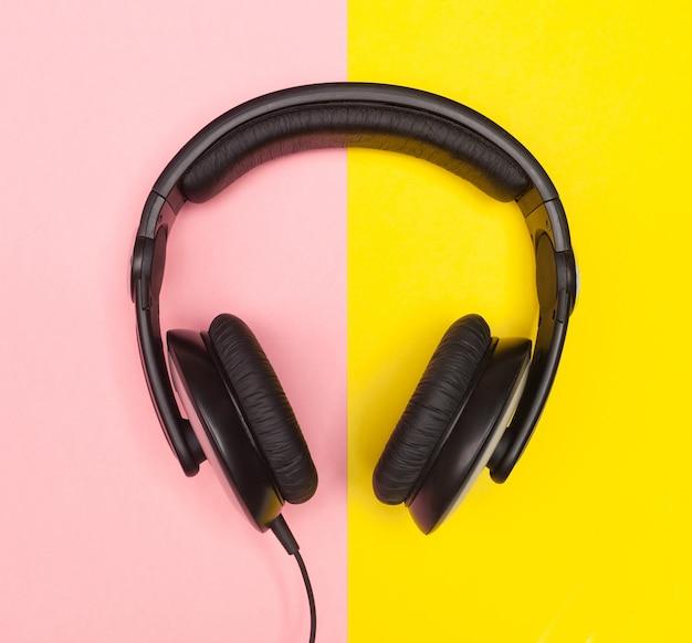 Hoofdtelefoons op roze en gele achtergrond.