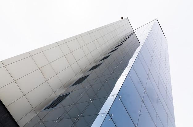 Hoog appartementengebouw, uitzicht op de grond. betegelde gevel met glazen oppervlak.