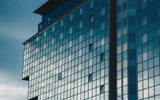Hoog gebouw. de lucht wordt weerspiegeld in de ramen van een hoog huis.