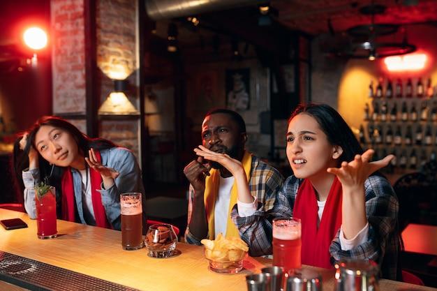 Hoog gespannen. groep vrienden kijken naar sport match samen in bar. emotionele fans juichen voor favoriete team, voetbal. concept van vriendschap, vrijetijdsbesteding, emoties. wedden, financiën, plezier.