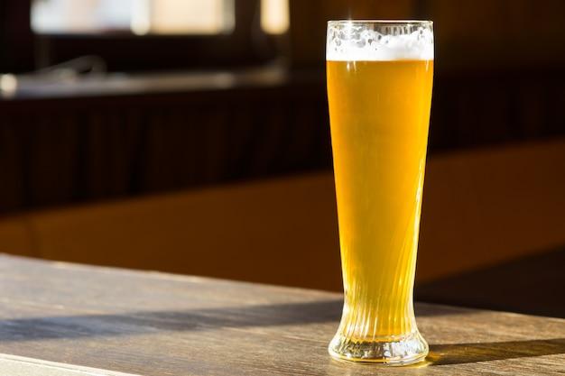 Hoog glas bier in sunray op tafel