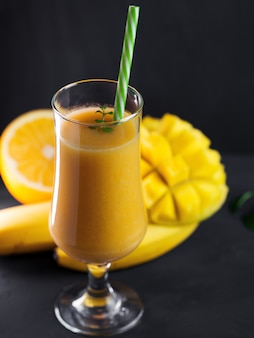 Hoog glas smoothie cocktail met mangosinaasappel en banaan. exotisch gezond ontbijt