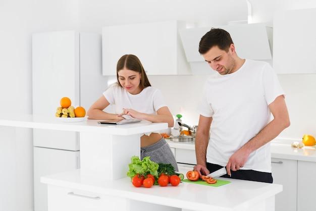 Hoog hoek jong paar dat salade voorbereidt