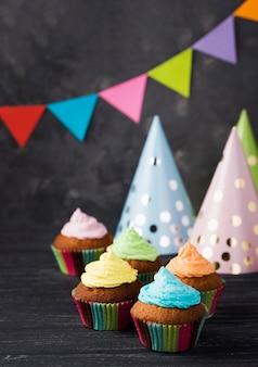 Hoog hoekassortiment met muffins met kleurrijk glazuur