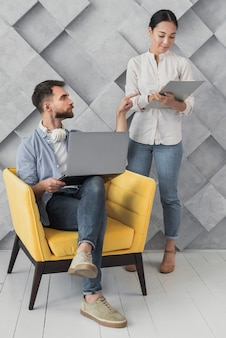 Hoog hoekmannetje op stoel die met collega spreekt