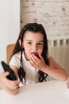 Hoog hoekmeisje dat koekjes eet en camera bekijkt