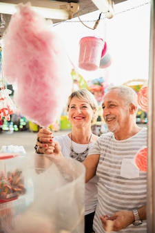 Hoog hoekpaar dat roze gesponnen suiker koopt