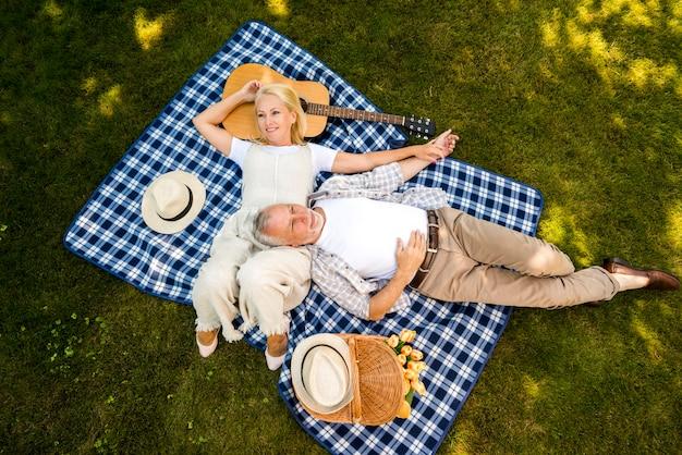 Hoog hoekpaar die van hun picknick genieten