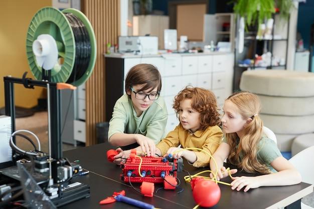 Hoog hoekportret van drie kinderen die samen een robotboot bouwen tijdens de techniekles op de moderne school, kopieer ruimte