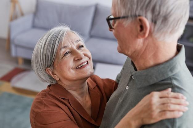 Hoog hoekportret van een liefdevol senior koppel dat samen thuis danst en elkaar met liefde aankijkt