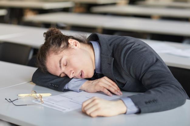 Hoog hoekportret van een uitgeputte jonge man die aan het bureau op school slaapt terwijl hij examens aflegt, kopieer ruimte
