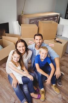 Hoog hoekportret van glimlachende familie met kartondozen