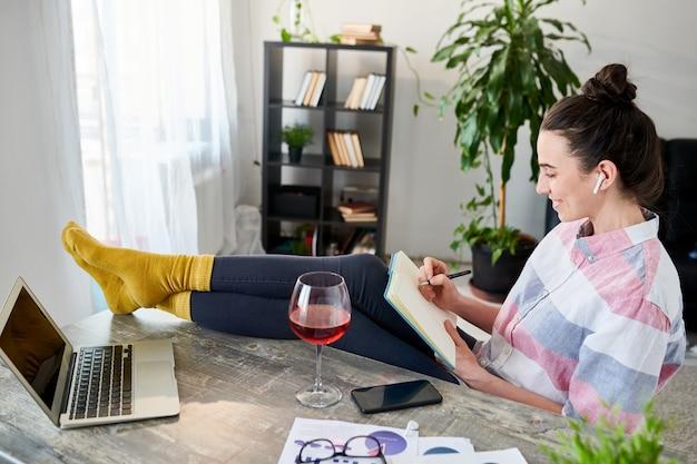 Hoog hoekportret van het ontspannen jonge vrouw schrijven in dagboek met voeten op bureau, exemplaarruimte