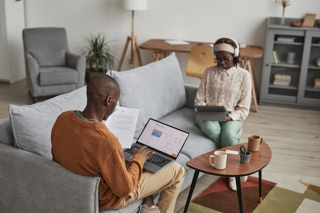 Hoog hoekportret van modern afrikaans-amerikaans stel dat apparaten gebruikt terwijl u thuis op de bank ontspant, focus op man die laptop gebruikt met online bankservice op scherm, kopieer ruimte