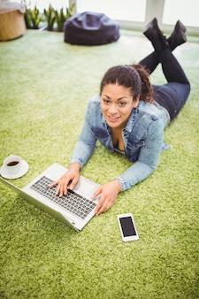 Hoog hoekportret van onderneemster die laptop in bureau met behulp van