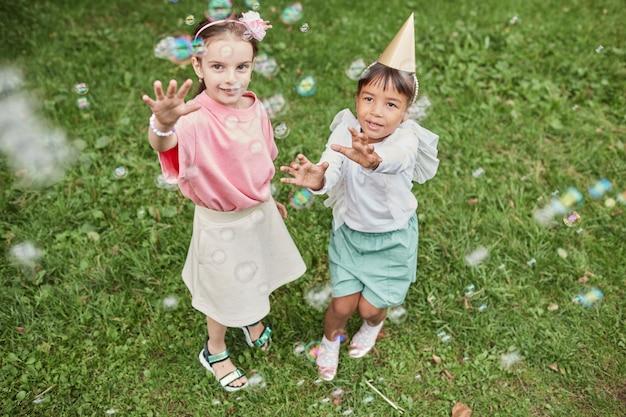 Hoog hoekportret van twee kleine meisjes die met bubbels spelen terwijl ze buiten genieten van een verjaardagsfeestje...