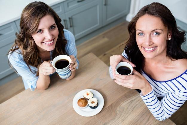 Hoog hoekportret van vrouwelijke vrienden die koffiemokken houden