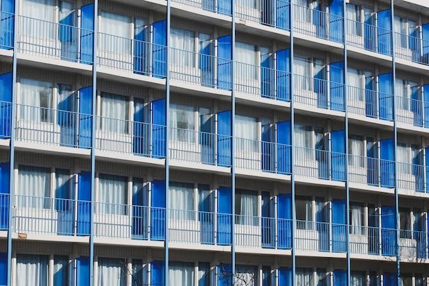 Hoog hotelgebouw met balkons met metalen hekken