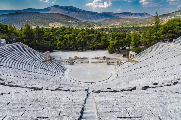 Hoog schot van een amfitheater gemaakt van steen met groene bomen en bergen op de achtergrond