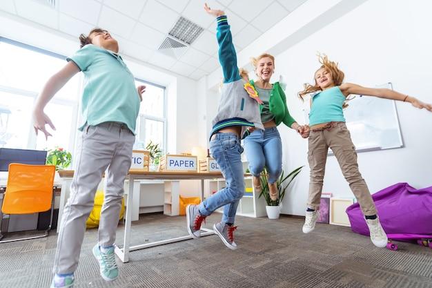 Hoog springen. drie gelukkige leerlingen en liefdevolle jonge leraar die hoog springt na het sorteren van afval waste