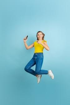 Hoog springen met smartphone. het portret van het kaukasische tienermeisje op blauw