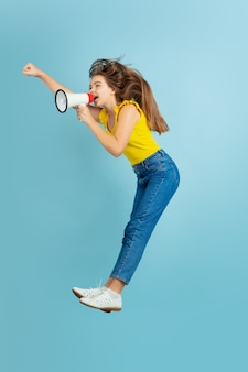 Hoog springen, om verkoop vragen. het portret van het kaukasische tienermeisje op blauw