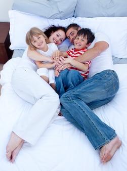 Hoog standpunt van ouders en kinderen die in bed ontspannen
