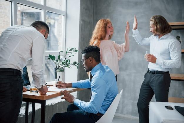 Hoog vijf. kantoormedewerkers boordevol werk en het schrijven van routine rapporten