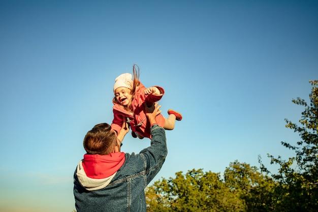 Hoog vliegen. gelukkige vader en kleine schattige dochter wandelen langs het bospad in zonnige herfstdag. familietijd, saamhorigheid, ouderschap en gelukkig kindertijdconcept. weekend met oprechte emoties.