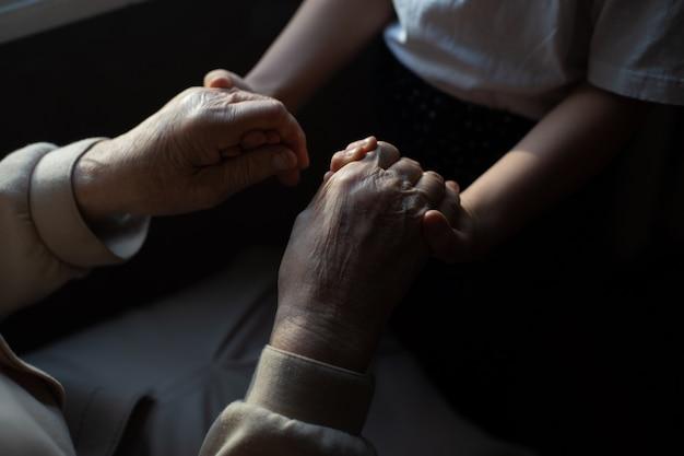 Hoogbejaarde overgrootmoeder en kleindochter houden elkaars hand vast