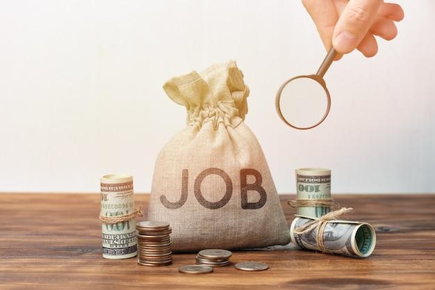 Hoogbetaalde baan zoeken concept. vergrootglas en geldzak.