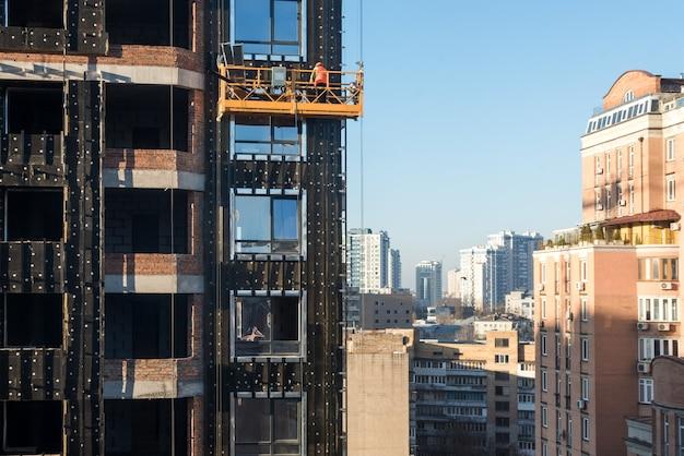 Hoogbouwwerkzaamheden, bouwplaatswerkers in wiegjes die met gevel werken, hangende wieg voor bouwers om buiten de wolkenkrabber te werken, bouwconstructie.