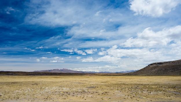 Hooggelegen landschap met ruw kaal landschap en schilderachtige dramatische hemel. brede hoekmening van bovenaf op 4000 m op de andes-hooglanden, peru.