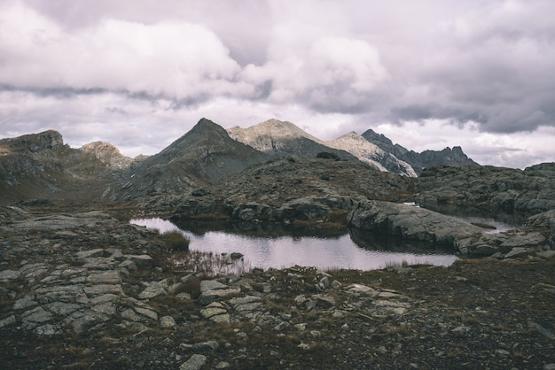 Hooggelegen rotsachtig landschap en meertje. majestueus alpien landschap met dramatische stormachtige hemel. brede kijkhoek van bovenaf, getinte afbeelding, vintage filter, gesplitste toon.
