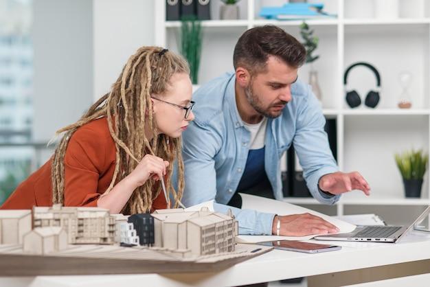 Hoogopgeleide hardwerkende creatieve mannelijke en vrouwelijke ontwerpers die werken met mock-up van toekomstige gebouwen