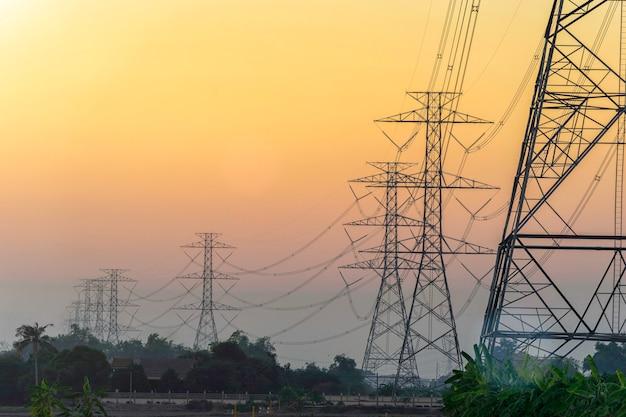 Hoogspanning elektrische polen op zonsonderganghemel