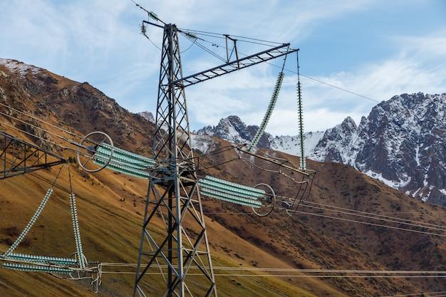 Hoogspannings elektrische isolatie elektrische lijn tegen de blauwe lucht en de bergen