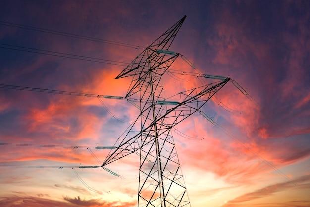 Hoogspannings elektrische paal en transmissielijnen bij zonsondergang