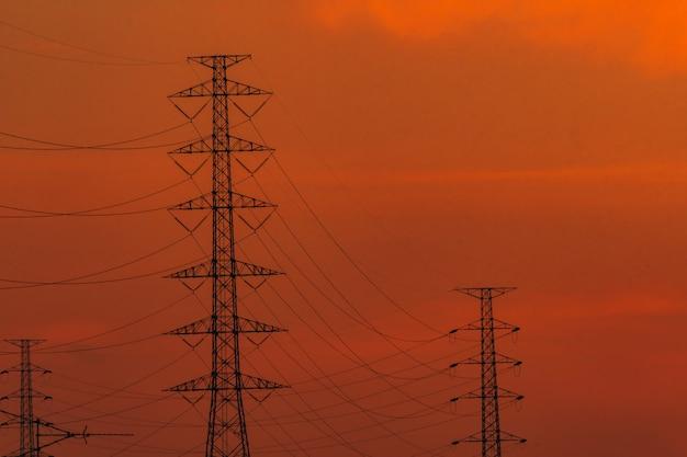 Hoogspannings elektrische paal en transmissielijnen in de avond. elektriciteitspylonen bij zonsondergang. kracht en energie. energiebehoud. hoogspanningsnettoren met draadkabel bij distributiestation.